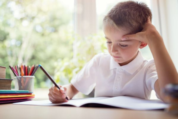 como-estudiar-con-ninos-en-casa-nino-estudia-con-lapiceros-de-color-istock