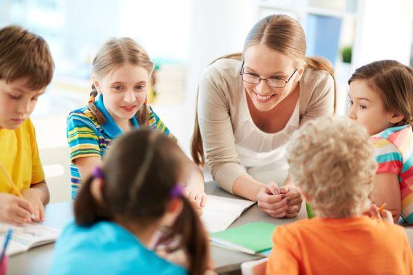 repaso-lengua-1o-eso-temario-profesora-con-gafas-habla-con-alumnos-istock