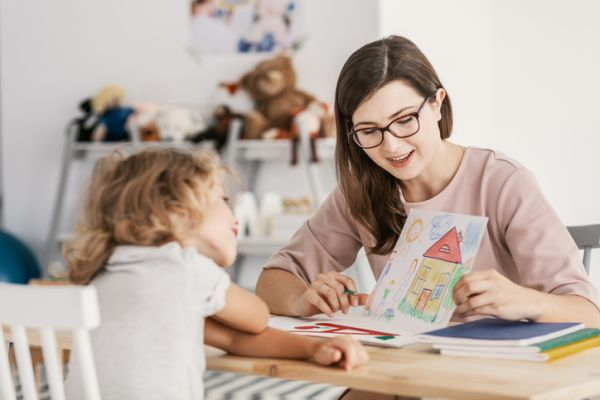 Terapeuta con niña y dibujo