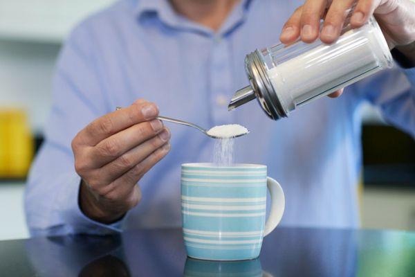Hombre echando azúcar en una taza