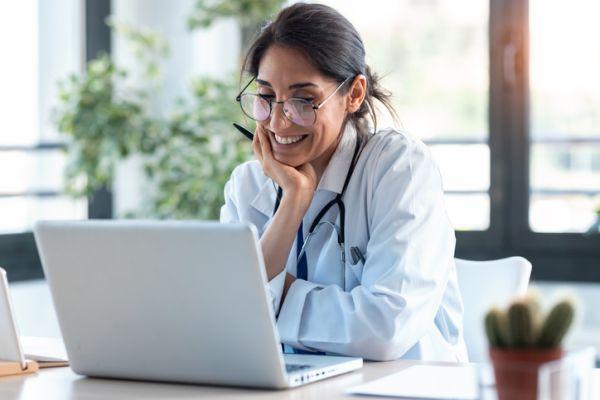Doctora sonriendo mirando el ordenador